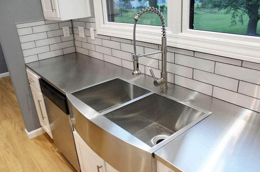 Kitchen with stainless steel countertops, apron sink, white cabinets and subway tile backsplash
