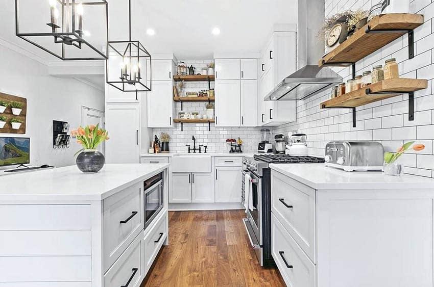 Kitchen with white subway tile backsplash white cabinets and white quartz countertops