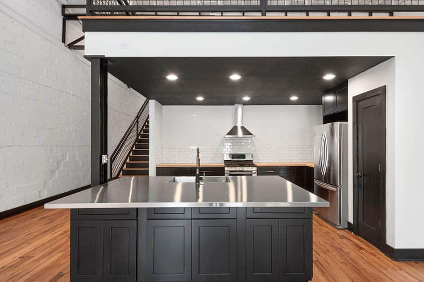 Loft kitchen with stainless steel countertops dark wood cabinets white subway tile backsplash