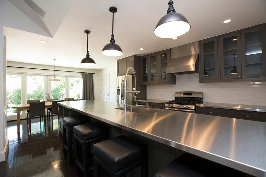 Modern kitchen with stainless steel counters subway tile and dark gray cabinets