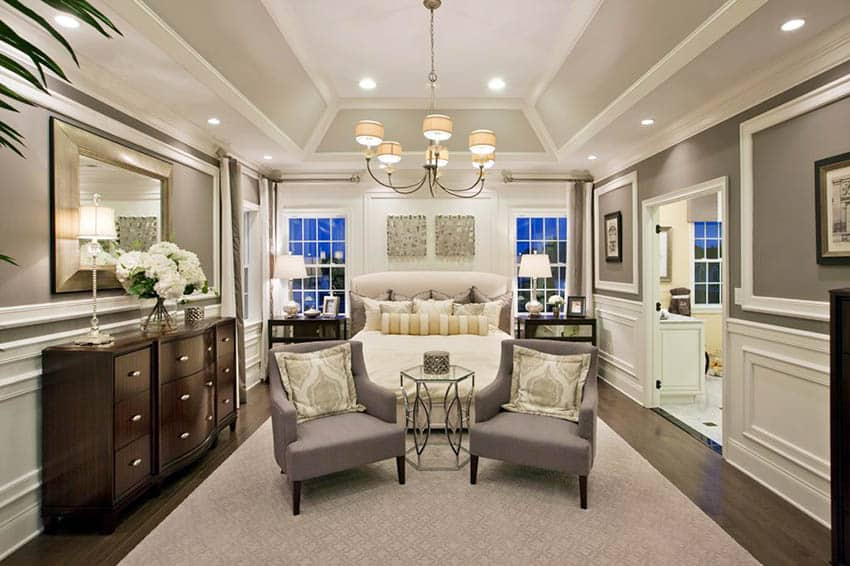 Bedroom with angled tray ceiling, wood flooring and wainscoting