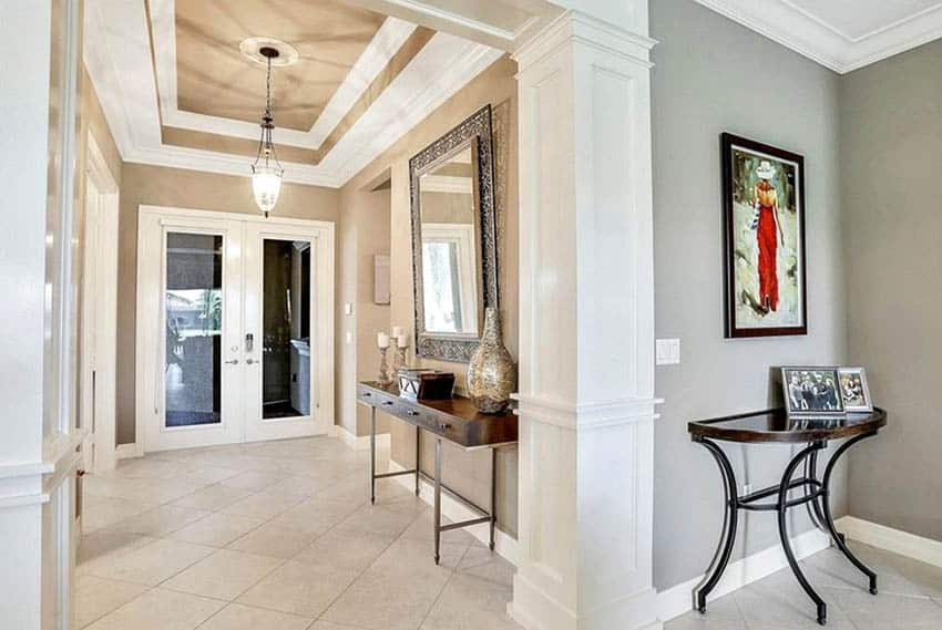 Foyer with tray ceiling and tile flooring