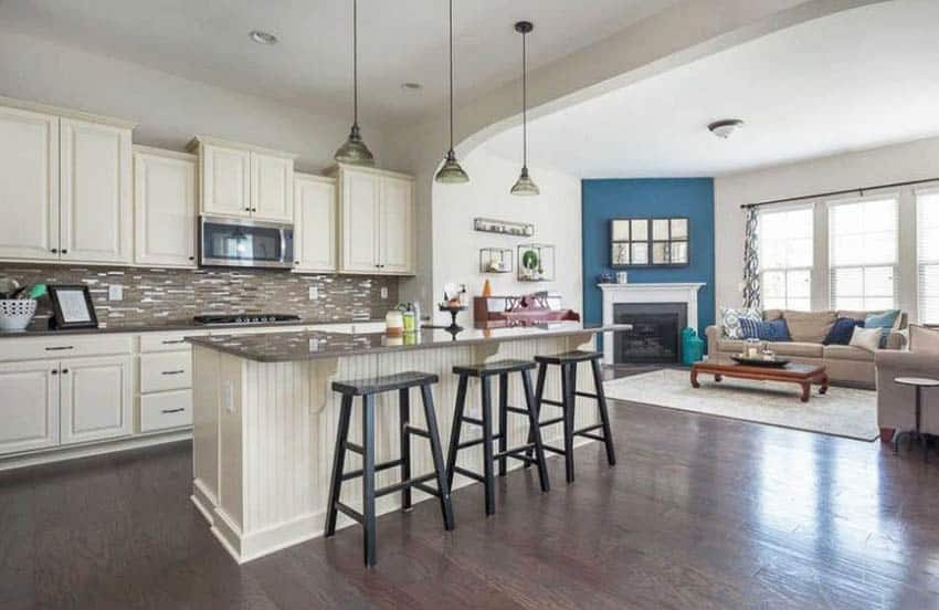 Kitchen with cream cabinets and beadboard island with pendant lighting