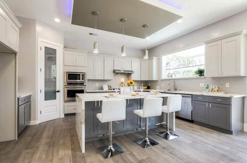 Kitchen with reverse tray ceiling with neon lights, white cabinets, gray island and quartz countertop