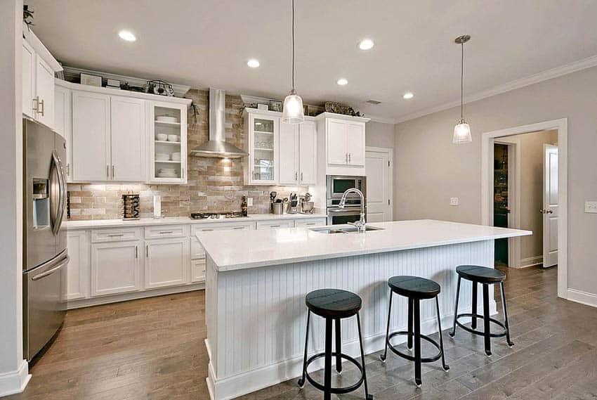 Kitchen with white shaker cabinets, beadboard island and quartz countertops