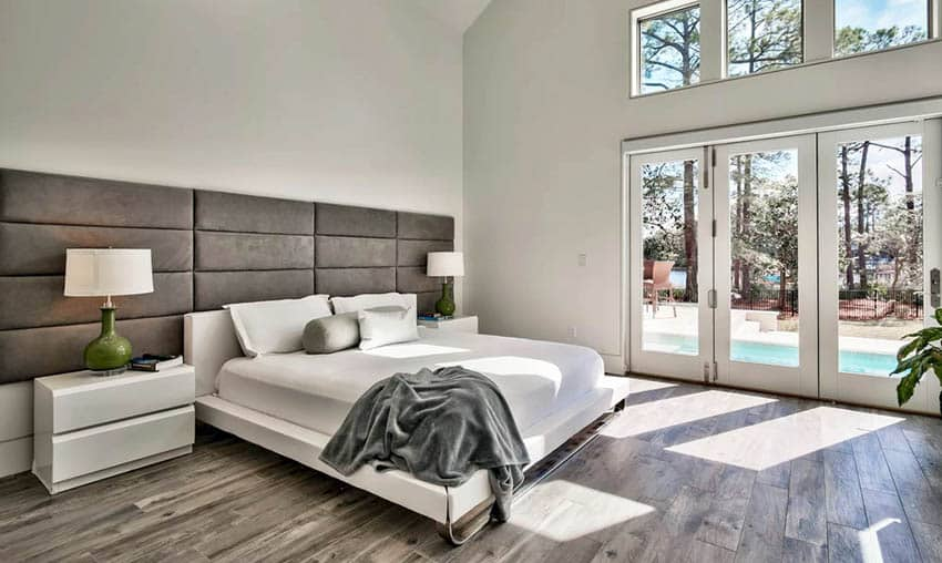 Master bedroom with hardwood flooring large bed headboard