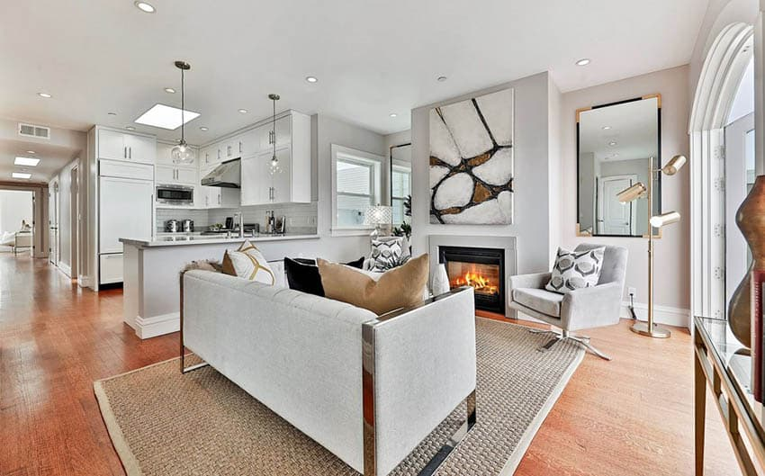 Open concept living room with fireplace and white cabinet kitchen