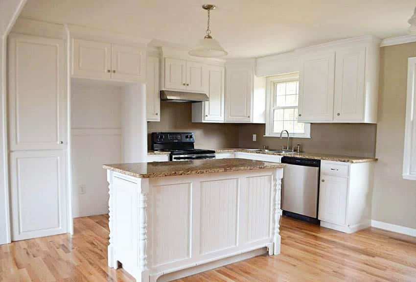 Traditional kitchen with white mdf cabinets beadboard island with columns and granite countertops