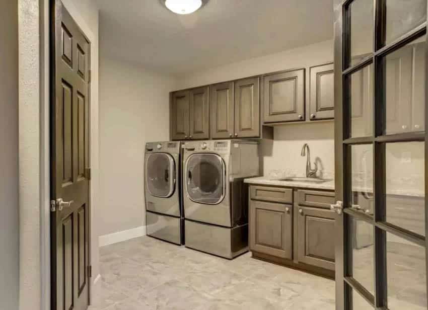 Basement laundry room with french doors, sink and wood cabinetry