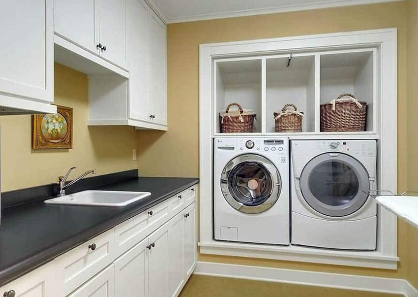 Basement laundry with recessed washer dryer with above storage and cabinets