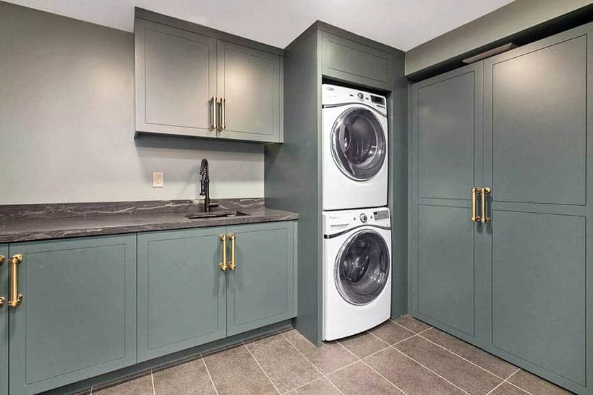 Custom laundry room with green cabinets quartz countertop and sink