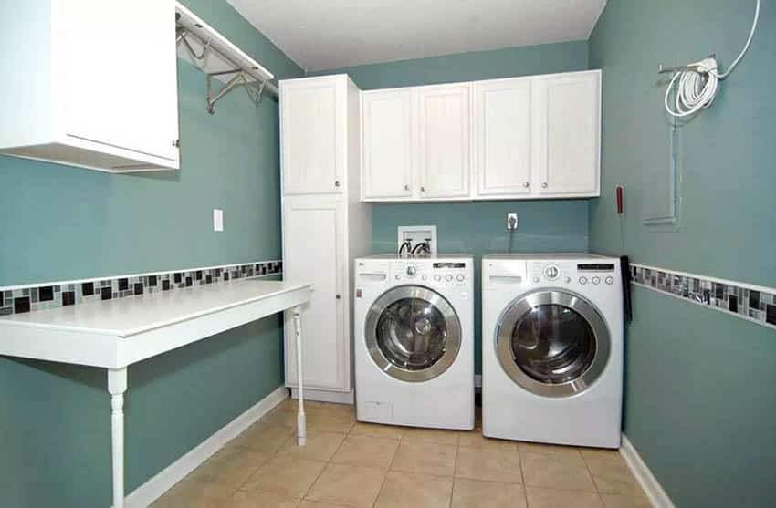 Finished laundry room with cabinets green wall paint