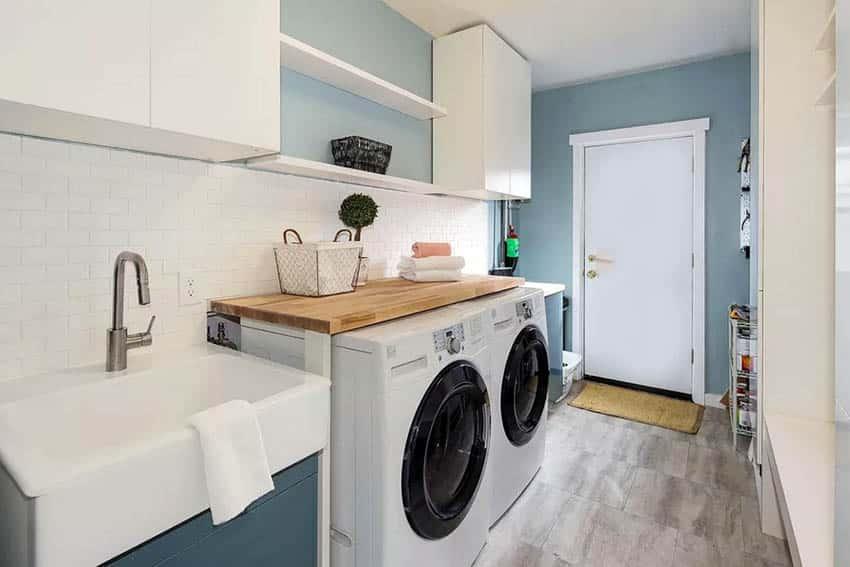 Laundry room with washer dryer wood surround sink subway tile backsplash