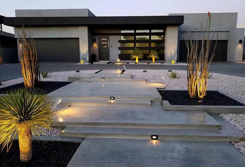 Modern home with desert landscape lighting