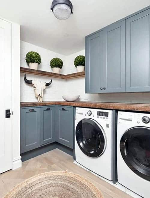 Small laundry room with blue cabinets wood shelving and plants