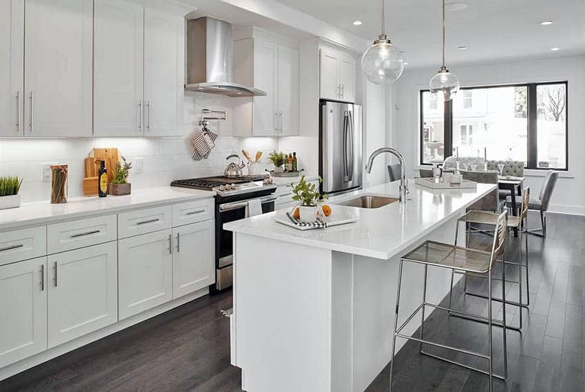White kitchen with shaker style cabinets, stainless steel hinges and hardware