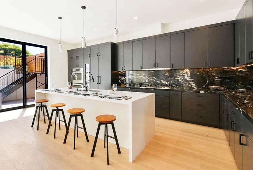 Contemporary kitchen with European style cabinet hinges, black cabinets and white island