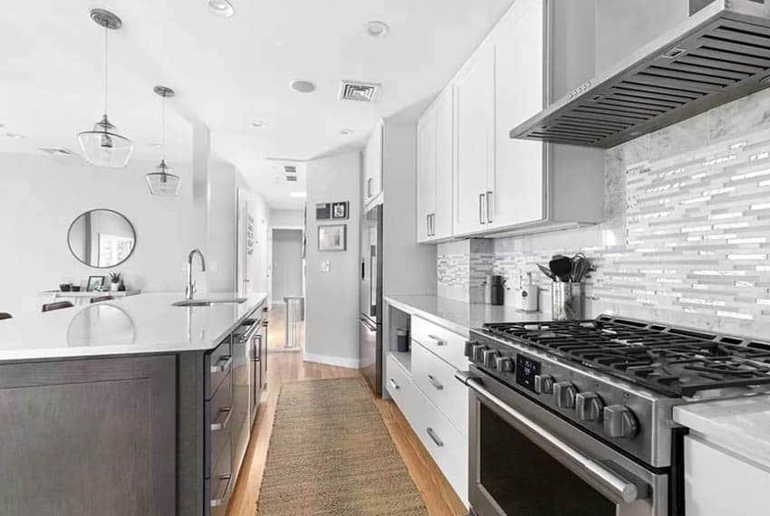 Contemporary kitchen with white cabinets, wood island and tile backsplash