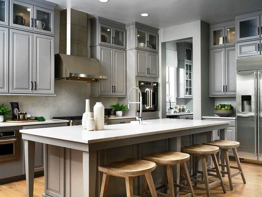 Kitchen with gray raised panel cabinets white quartz counter island
