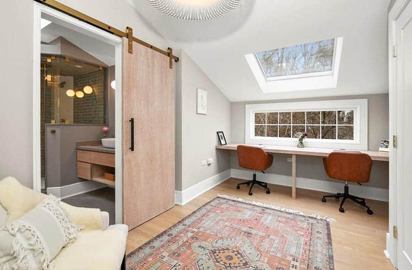 Attic home office with built in desk window view and skylight