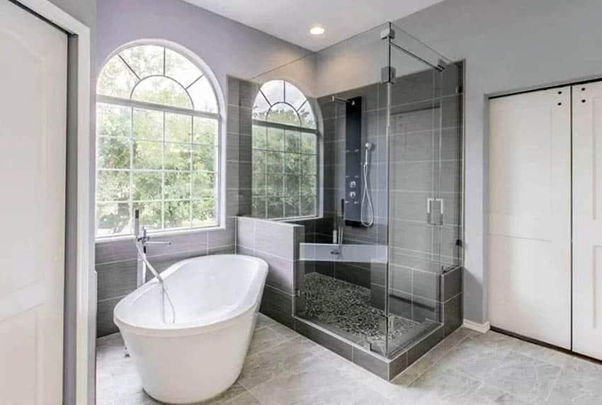 Bathroom with black pebble tile floor and freestanding bathtub