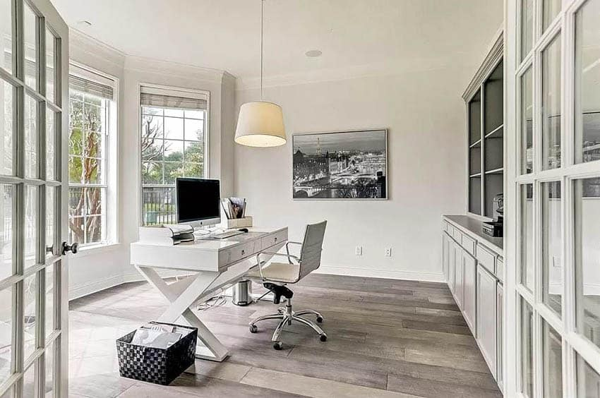 Bright home office with built in wall unit french doors