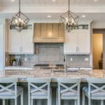 Contemporary kitchen with running bond tile with inlay over oven