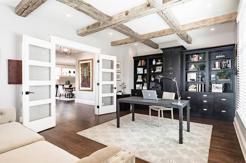 Home office with black built in cabinets, modern french doors and wood beam ceiling