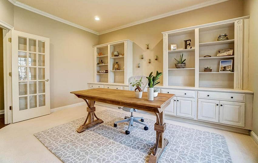 Home office with built in wall cabinets shelving and french doors