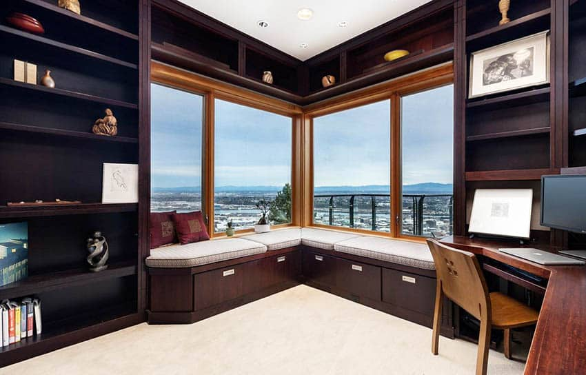 Home office with dark wood built in desk shelves and window seat