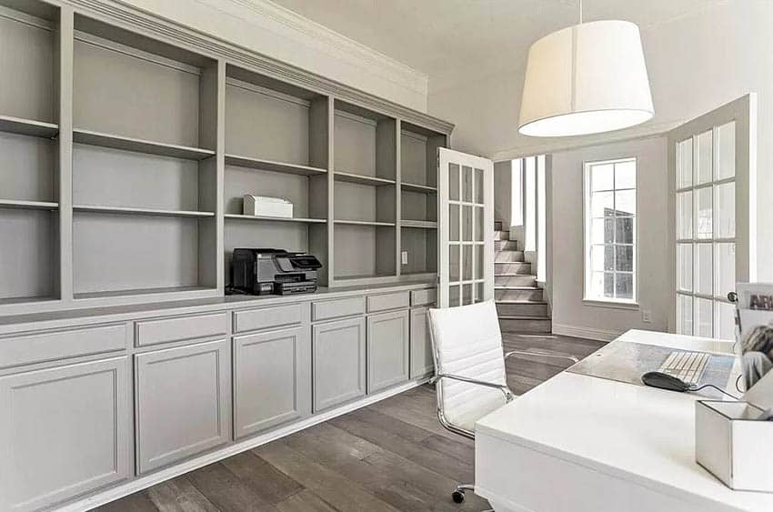 Home office with gray built in cabinet white desk and french doors