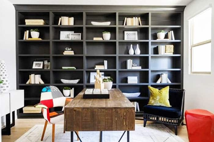 Home office with rustic desk and black built in shelving