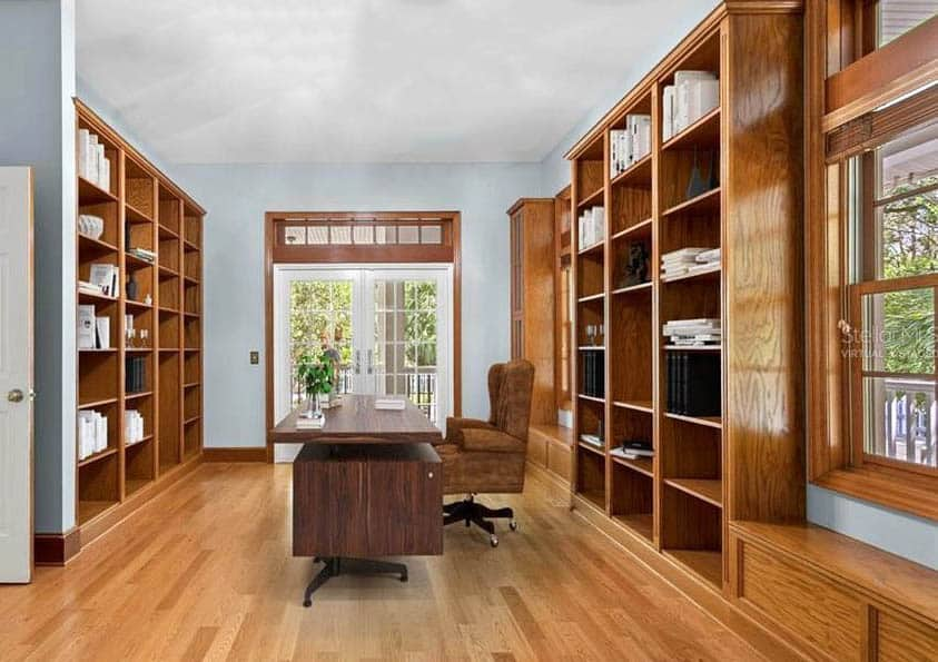 Large home office with wood built in shelving center desk