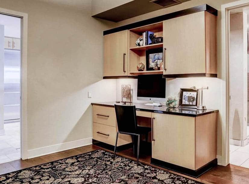 Office room with built in light wood desk and wall cabinets
