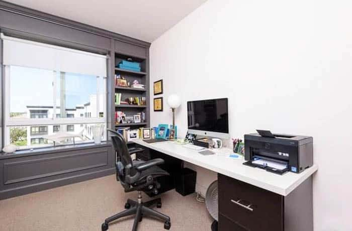 Small home office with built in shelving paneling wall