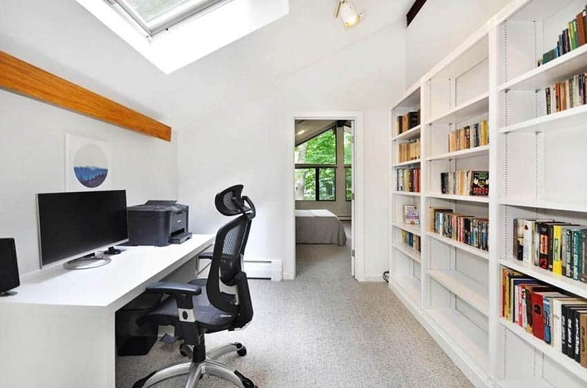 Upstairs office with skylight and wall of shelving