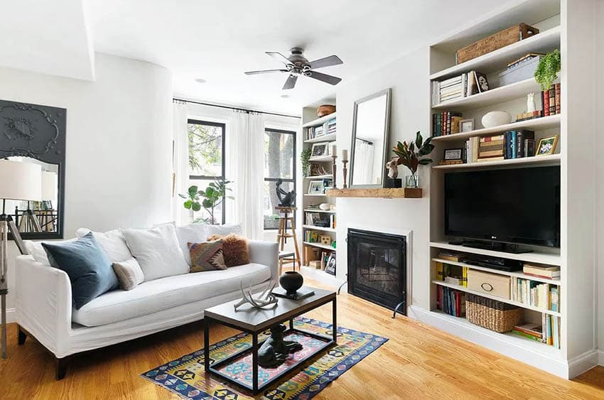 Cottage living room with built in bookshelves fireplace mantle and decor items