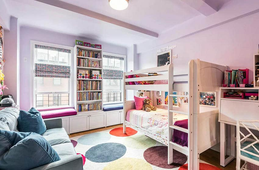 Girls bedroom with built in bookshelves and window seats
