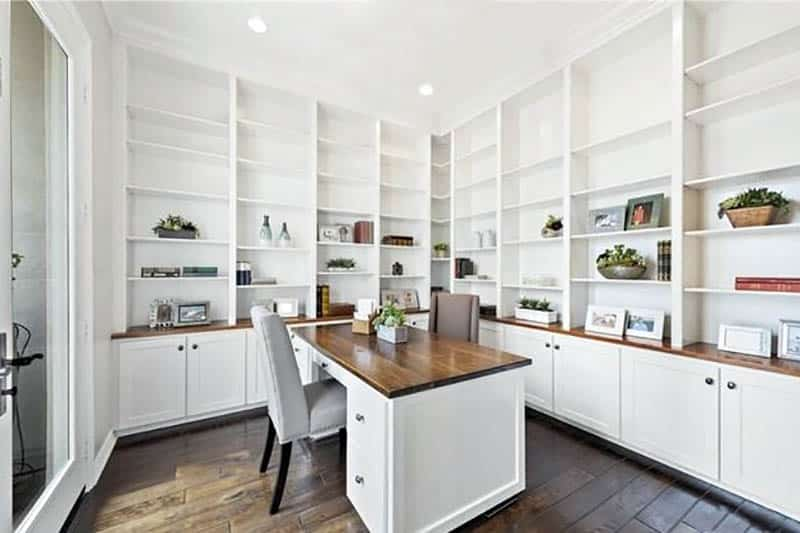 Home office with floor to ceiling built in bookshelves and cabinets