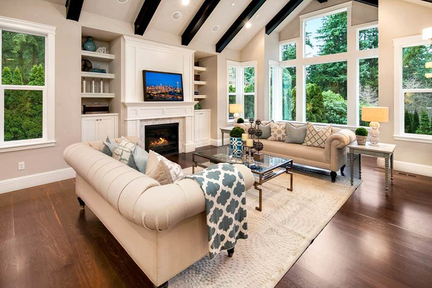 Living room with built in bookshelf and fireplace hickory floors and vaulted ceiling