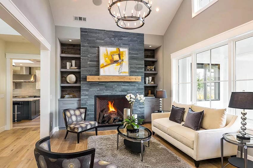 Living room with slate fireplace and gray built in bookshelves with cabinets