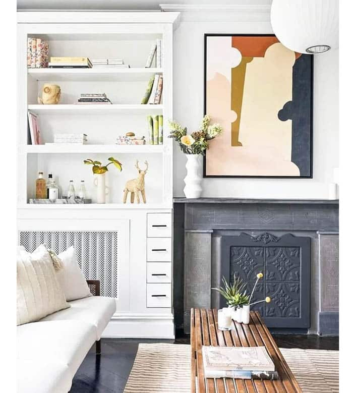 Living room with white built in bookshelves next to fireplace