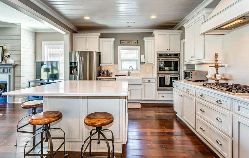 White kitchen with wood plank ceiling and wood tile flooring