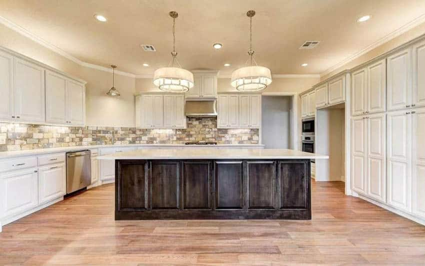 beige-kitchen-cabinets-with-dark-wood-island-brick-tile-backsplash-wood-flooring