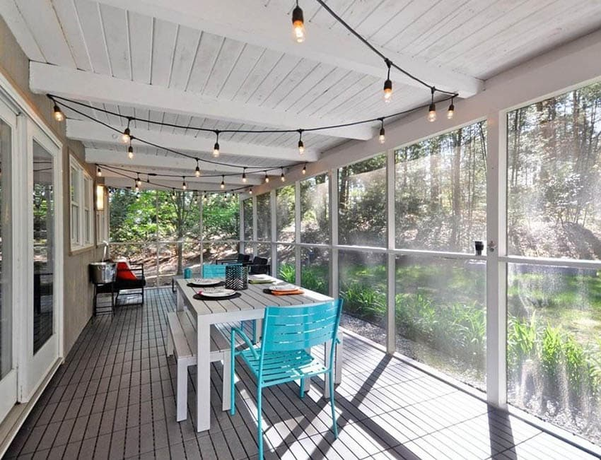 Enclosed screen patio with white plank ceiling string lights and dining table