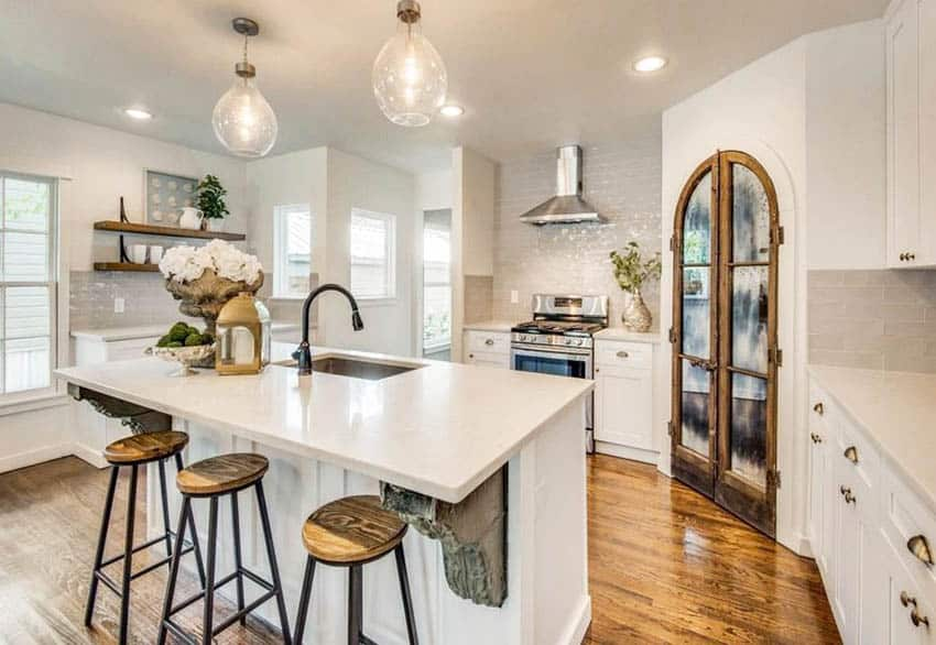Kitchen with custom arched wood pantry door, white cabinets and white quartz countertops
