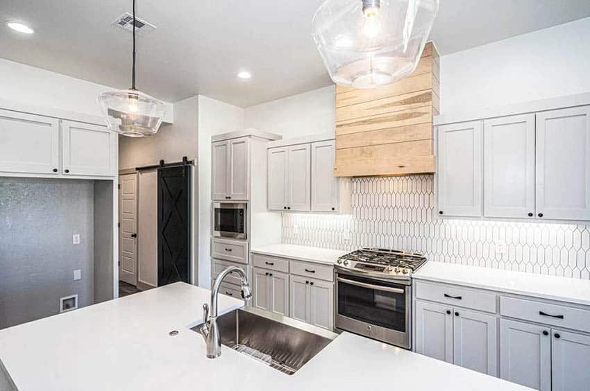 Kitchen with light gray cabinets white quartz countertop