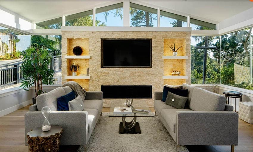 Living room with stone built in shelving with recessed lighting
