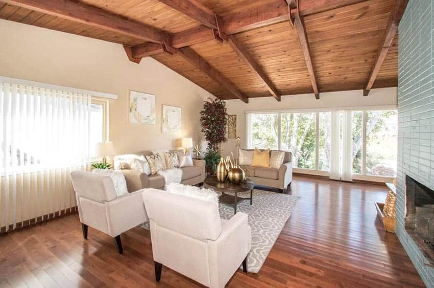 Living room with tongue and groove wood vaulted ceiling and painted brick fireplace
