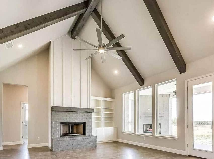 Living room with vaulted ceiling wood beams recessed lighting and hanging fan